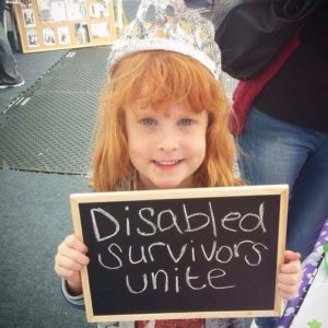 Little girl wearing a princess crown holding up black board sign on it which says 'Disabled Survivors Unite'.
