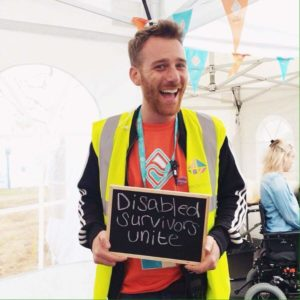 Charlie smiling in high vis jacket holding up black board sign on it which says 'Disabled Survivors Unite'.
