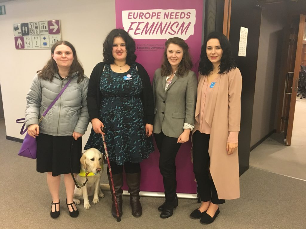 "Photo of Holly, guide dog Isla, Ashley, Bekki, and Alice. Stood in front of pink ""EUROPE NEEDS FEMINISM"" sign."